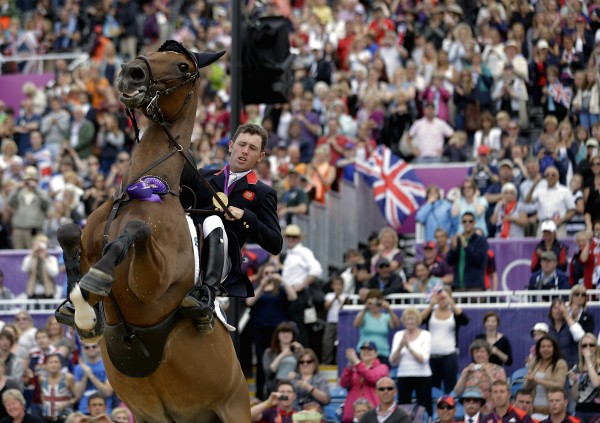 Hello Sanctos, the horse ridden by Scott Brash, of Great Britain, rears as the crowd cheers during a victory lap after Great Britain won the gold medal for the equestrian team show jumping at the 2012 Summer Olympics on Monday, Aug. 6, 2012, in London.