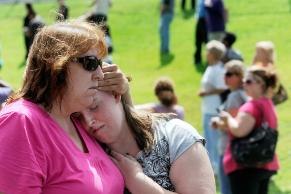 Tracie Bradford, of Perry Hall, Md., consoles her daughter Leah, a student at Perry Hall High School who says she was in the school's cafeteria when a student was shot there and critically wounded on the first day of classes, Monday, Aug. 27, 2012. A suspect was taken into custody shortly after the shooting, according to police. No one else was reported injured.