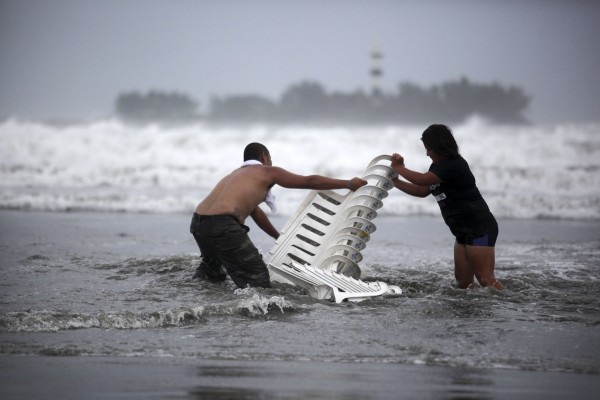Vendors that were caught unprepared try to recover their chairs after high waves dragged their beach stalls into the sea in Veracruz, Mexico on Thursday, Aug. 9, 2012.  Tropical Storm Ernesto headed into Mexico's southern Gulf coast as authorities in the flood-prone region prepared shelters, army troops and rescue personnel for drenching rains.
