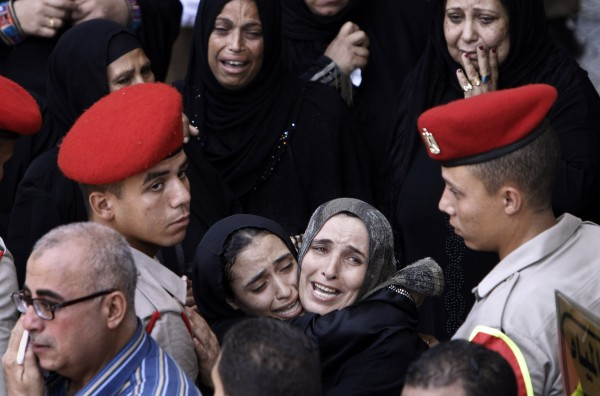 Egyptian women mourn during the military funeral of 16 Egyptian soldiers who were killed Sunday, Aug. 5, 2012 during an attack at a checkpoint along the Sinai border with Israel by Islamic militants with purported ties to Gaza, in Cairo, Egypt on Tuesday, Aug. 7, 2012. Mourners prayed for the dead at a mosque in an east Cairo suburb on Tuesday. The coffins, wrapped in Egypt's red-white-and-black flag, were later taken to a nearby square where a military ceremony is under way.