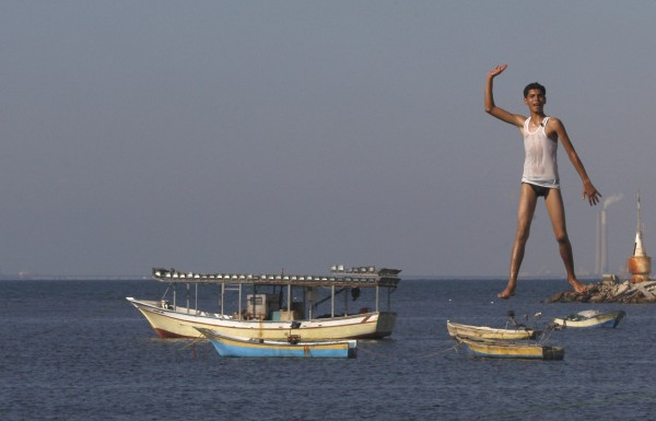 A Palestinian youth jumps into the Mediterranean sea on the beach at the port of Gaza City, Gaza on Monday, Aug. 27, 2012.