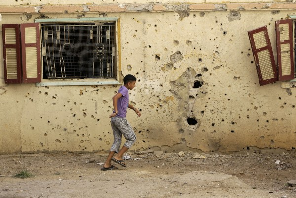 A Lebanese boy walks past a house that was hit by rockets on a frontline street where clashes erupted between pro- and anti-Syrian regime groups, in the northern city of Tripoli, Lebanon on Thursday, Aug. 23, 2012. The latest clashes were between gunmen from the Sunni neighborhood of Bab Tabbaneh and the neighboring Jabal Mohsen, which is mostly populated by followers of the Alawite sect, an offshoot of Shiite Islam. The clashes that began Monday left at least a dozen people dead and dozens more wounded.
