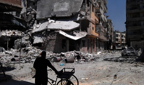 In this citizen journalism image provided by Shaam News Network SNN, taken on Saturday, Aug. 11, 2012, a man looks at destroyed building from Syrian forces shelling in Khaldiyeh, Homs, Syria.