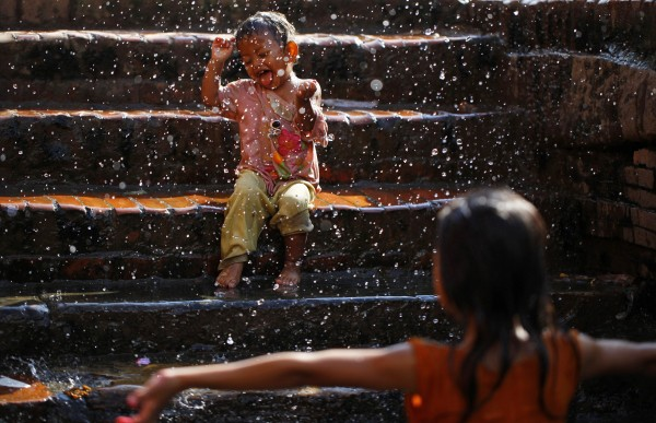 A boy reacts as his sister splashes water from a stone spout near Bangalamukhi temple in Katmandu, Nepal on Tuesday, Aug. 28, 2012. There are dozens of centuries-old stone spouts that are still used to collect household water or as public bathing spots in the city.