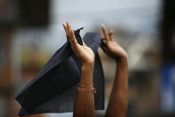 A protester of Nepal Youth Front, the student organization of Communist Party of Nepal (Unified Marxist-Leninist), displays a black flag outside the airport in Katmandu, Nepal on Wednesday, Aug. 29, 2012, as Nepalese Prime Minister Baburam Bhattarai leaves for Iran to attend the Non-Aligned Movement summit. Bhattarai has been running a caretaker government since May, but the opposition parties want him to step down and for a new government with representation from all the major political parties to conduct elections scheduled for later this year.