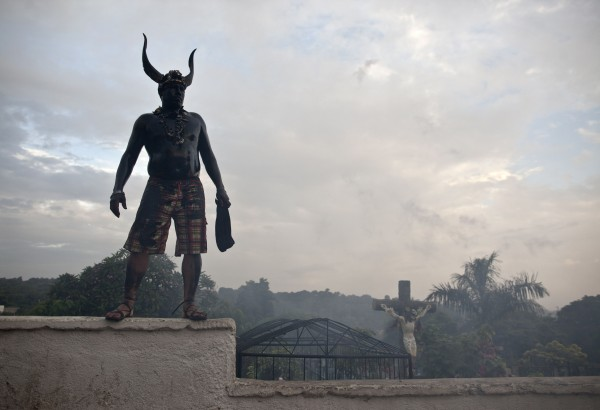 "A ""promesante"" or promiser, dressed as a devil with his body coated in a mix of grease and motor oil, stands on a cemetery wall to get a better view of a procession during Santo Domingo festivities in Managua, Nicaragua on Wednesday, Aug. 1, 2012. Some of the faithful annually coat their bodies in a black lubricant as a promise for a prayer or miracle they believe was performed or answered by Managua's patron saint, Santo Domingo de Guzman. The first 10 days of August are reserved for the carnival-like celebration to honor the patron saint with processions, bullfights, parties and church services."