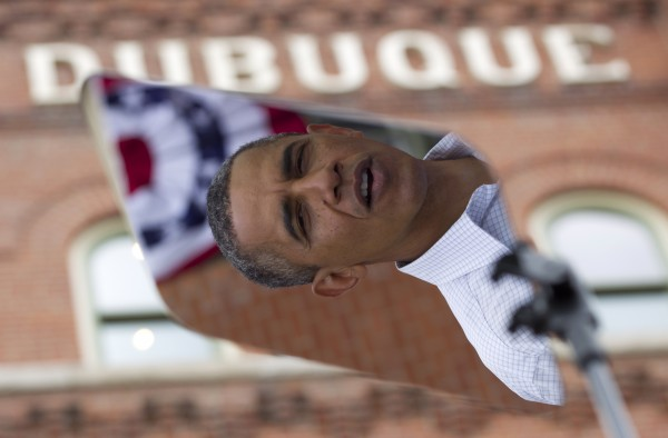 President Barack Obama is seen reflected in a teleprompter on stage during a campaign event at the Alliant Energy Amphitheater on Wednesday, Aug. 15, 2012, in Dubuque, Iowa, during a three-day campaign bus tour through Iowa.