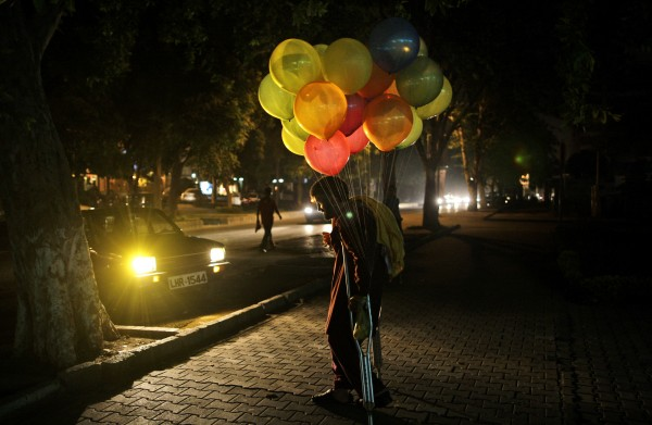 Pakistani vendor Sayed Anwar, 36, stands on a roadside hoping to sell balloons, in Islamabad, Pakistan on Wednesday, Aug. 8, 2012.
