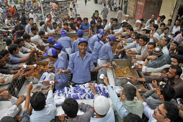 Pakistanis buy food from a stall to break their fast, during the Muslim holy fasting month of Ramadan, in Karachi, Pakistan on Tuesday, Aug. 7, 2012.