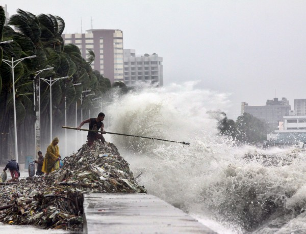A man holding a pole stay on the mound of garbage washed ashore by big waves as others look for recyclable materials Wednesday, Aug. 1, 2012 along Roxas Blvd. in Manila, Philippines. The slow-moving Typhoon Saola killed at least 12 people and displaced 154,000 in the Philippines.