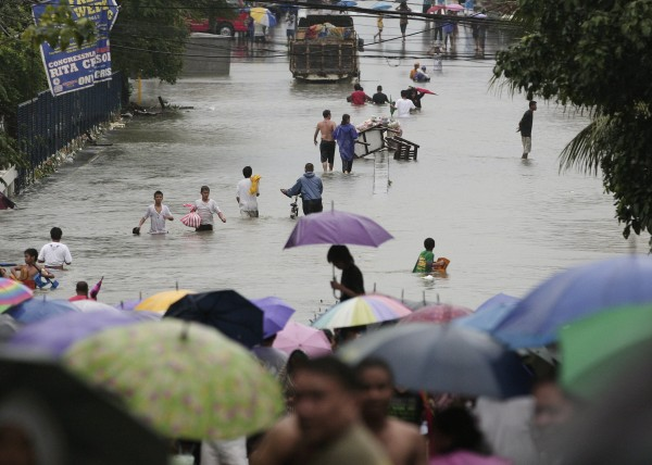 Residents wade along flooded roads in Quezon City, north of Manila, Philippines, on Tuesday Aug. 7, 2012. Relentless rains submerged half of the sprawling Philippine capital, triggered a landslide that killed several people and sent emergency crews scrambling Tuesday to rescue and evacuate tens of thousands of residents.