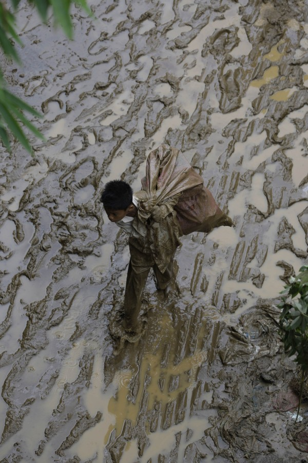 A Filipino boy walks along a muddy road after flooding in suburban Quezon city, north of Manila, Philippines on Friday, Aug. 10, 2012. About 2.4 million people in Manila and nearby provinces were affected by Manila's worst flooding since 2009 as more than half of the sprawling metropolis of 12 million was submerged at the peak, and schools and offices have been closed for days.