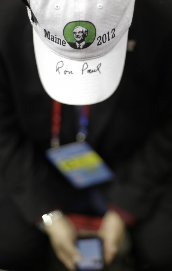With Ron Paul's autograph on his hat, Maine delegate Bryan Daugherty from Bangor looks at his smart phone at the Republican National Convention in Tampa, Fla., on Tuesday, Aug. 28, 2012.