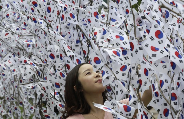 A woman watches national flags displayed on trees ahead of a celebration day of Korea's liberation from Japan''s colonial rule, in front of Songpa-Gu Office or an old capitol of Korea in Seoul, South Korea on Tuesday, Aug. 14, 2102. Liberation Day falls on Aug. 15.