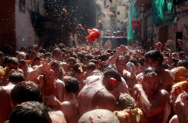 Revelers throw tomatoes during the annual &quottomatina&quot tomato fight fiesta in the village of Bunol, near Valencia, Spain on Wednesday, Aug. 29, 2012. Bunol's town hall estimated more than 40,000 people, some from as far away as Japan and Australia, took up arms Wednesday with 100 tons of tomatoes in the yearly food fight known as the 'Tomatina' now in its 64th year.