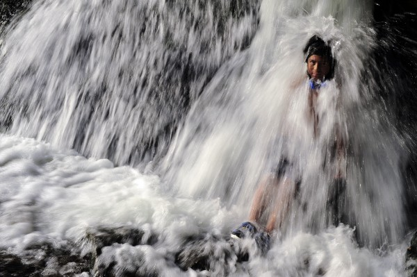 A boy cools off under a waterfall on the Arga River,  in Pamplona, northern Spain on Thursday, Aug. 23, 2012.