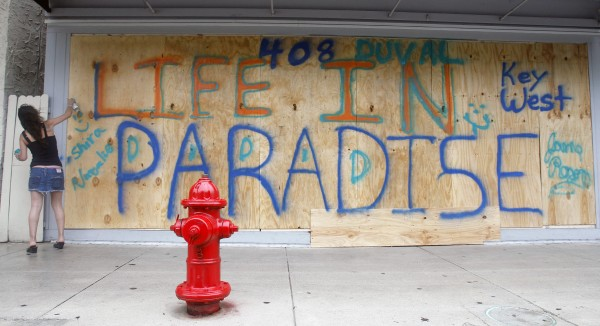 Shira Edllan Gervasi of Israel puts her name on plywood protecting a storefront in Key West, Fla., in anticipation of Tropical Storm Isaac on Saturday, Aug. 25, 2012.  Isaac's winds are expected to be felt in the Florida Keys by sunrise Sunday morning.