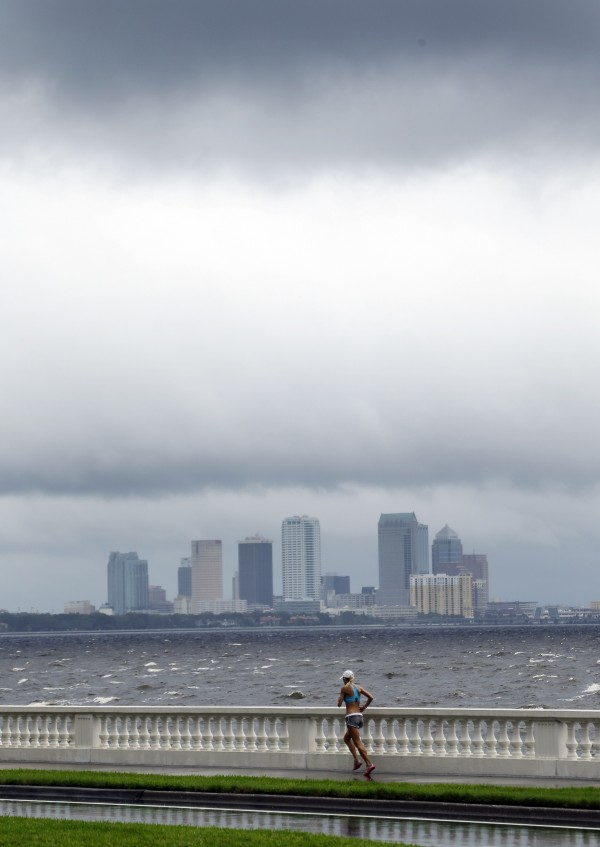 A woman jogs along Bayshore Boulevanrd in between squalls blowing across the bay in Tampa, Fla., on Monday, Aug. 27, 2012. The Republican National Convention has delayed its start because of the approaching tropical storm Isaac which is churning it's way across the Gulf of Mexico.