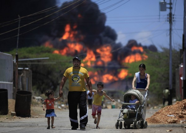 Members of a family walk on a street as flames rise after an explosion at the Amuay refinery near Punto Fijo, Venezuela on Sunday, Aug. 26, 2012. Venezuelans who live next to the country's biggest oil refinery said they smelled a strong odor of sulfur hours before a gas leak ignited in an explosion on Saturday that killed at least 39 people and injured more than 80.