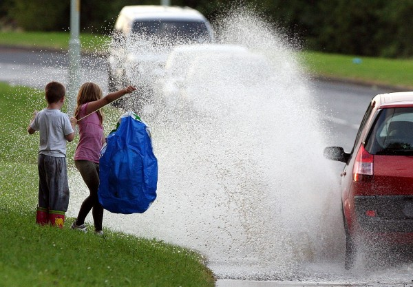 Children look on at a motorist driving through flood water as torrential downpours caused flash floods in Hebburn, England, Sunday, Aug. 5, 2012. Torrential downpours have caused flash floods across many parts of the UK.