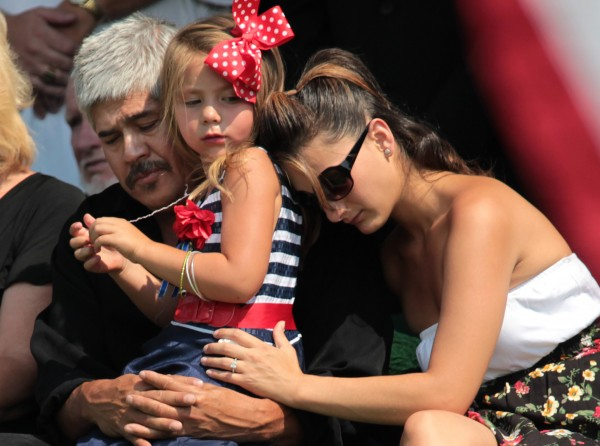 Family members of Colorado shooting victim Jonathan Blunk comfort his daughter, Hailey, 4, during a graveside service in Reno, Nev., Friday, Aug. 3, 2012. Blunk, who served three tours in the Middle East from 2004 to 2009, died after shielding a friend and telling her to stay down when a heavily armed gunman burst into the midnight showing of &quotThe Dark Knight Rises&quot in Aurora, Colo., killing 12 people and wounding or injuring 58 others. James Holmes, 24, a former doctoral student in neuroscience, was charged with dozens of counts of first-degree murder and attempted murder in the July 20 attack.