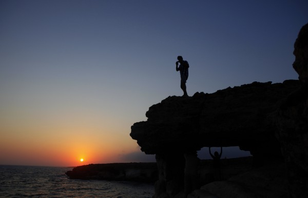 People enjoy the sunset by the sea at the caves area in Ayia Napa resort near Cavo Greco in southeast of capital Nicosia, Cyprus, Sunday, Aug. 5, 2012.