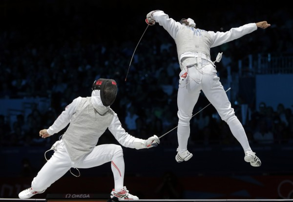 Ryo Miyake of Japan competes against  Andrea Baldini of Italy (right) in the gold medal match during the men's foil team fencing competition at the 2012 Summer Olympics, Sunday, Aug. 5, 2012, in London.