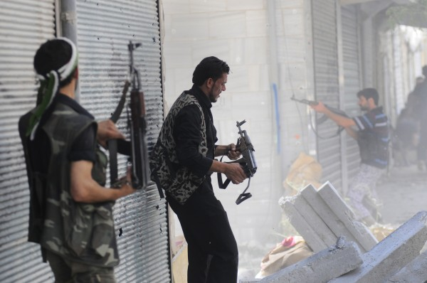 In this Wednesday, Aug. 1, 2012, photo, a Free Syrian Army soldier fires his weapon during clashes with Syrian government forces in Saladin neighborhood, in Aleppo, Syria.