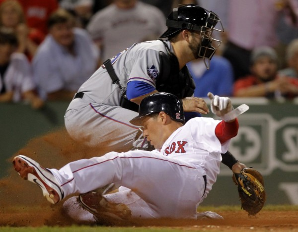 Boston Red Sox's Jacoby Ellsbury, front, scores on a double hit by Carl Crawford as Texas Rangers catcher Mike Napoli, rear, waits for the ball in the eighth inning of a baseball game at Fenway Park in Boston, Monday, Aug. 6, 2012.