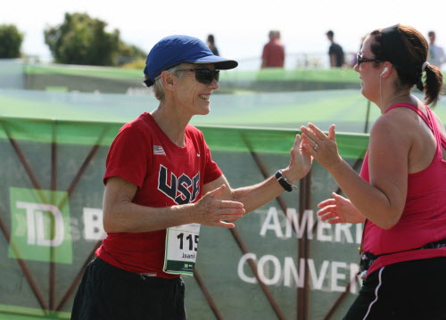 Joan Benoit Samuelson greets a runner as she crosses the finish line Saturday, Aug. 4, 2012 during the annual TD Bank Beach To Beacon 10K road race in Cape Elizabeth.