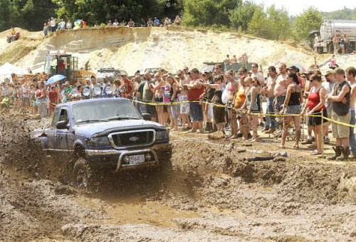 Spectators line the popular mud run as Chuck Spears of Orange, Mass., negotiates the course during the Redneck Blank in Hebron on Saturday, Aug. 4, 2012.
