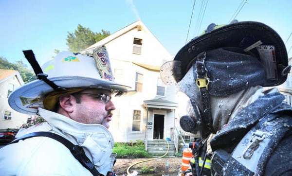 Battalion Chief Dean Milligan (left) of the Auburn Fire Department talks with firefighter Rob Dumont about the situation inside 116 Summer St. in Auburn just after exiting the third floor of the building.