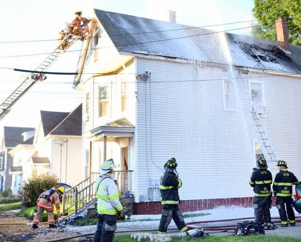 Lewiston and Auburn firefighters work to extinguish a two alarm fire at 116 Summer St. in Auburn Sunday morning.