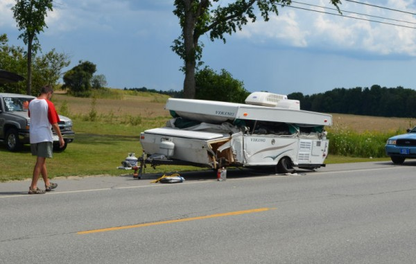 Todd Walker of Gorham talks on his cellphone as he walks toward his demolished pop-up camper after a three-vehicle crash on Route 7 in Corinna on Thursday, Aug. 9, 2012. Walker and his family were unhurt in the crash.