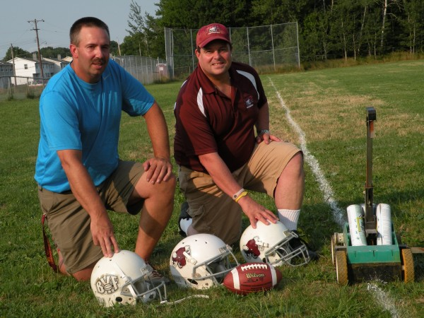 Coaches and board members Shawn Detour (left) and Brian Strout display some of Bangor Youth Football's equipment at their new practice field behind Downeast School on Moosehead Boulevard. Detour borrowed  the line painter to finish lining the field Friday, Aug. 17, 2012.