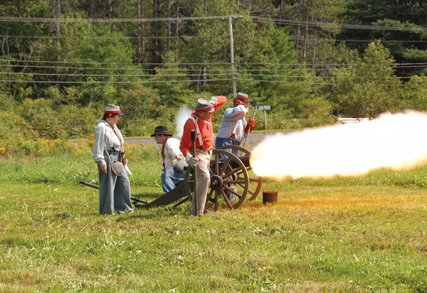 A Confederate artillery crew from the Richmond Howitzers fires a cannon at Union troops during a battle fought at the Good Will Hinckley School on Saturday, Aug. 25, 2012. The event was part of the two-day &quotWe Are Coming, Father Abraham&quot Civil War re-enactment.