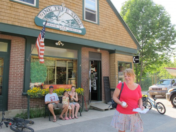 Locals in Grand Lake Stream said the annual financial summit at nearby Leen's Lodge is a financial and marketing boon for the plantation of 109. Deb Cochran (right), pictured at Pine Tree Shop, a general store that doubles as a post office, said the town is well-known to outdoorsmen, but not to many others.