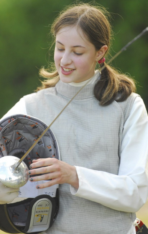 Joanna Garneau of Garland looks over her gear before putting on a fencing display aganist fencing instructor Cleon Grover at WLBZ 2 in Bangor on Wednesday afternoon, Aug. 1, 2012.