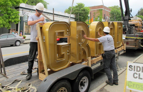 Workers from the Hudson, N.H., company Barlo Signs, prepare the final element of Ellsworth's Grand auditorium's restored marquee to be lifted into place by crane on Tuesday, Aug. 28, 2012.