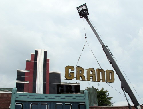 The final piece of the restored Grand auditorium marquee is lowered into place at the Ellsworth theater on Tuesday, Aug. 28, 2012.