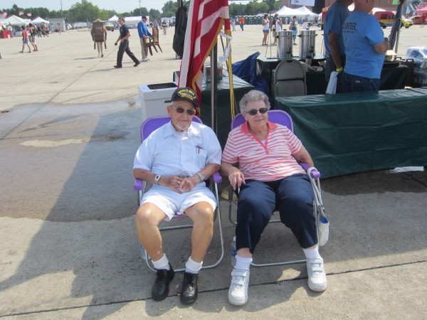 Harry Dixon, 89, and his friend, Thelma Lever, both of Lewiston, sit Saturday morning, Aug. 25, 2012 in the shade of an American Legion booth to watch Randy Harris maneuver his Skybolt 300 over the runway of the former Brunswick Naval Air Station during the 2012 Great State of Maine Air Show.