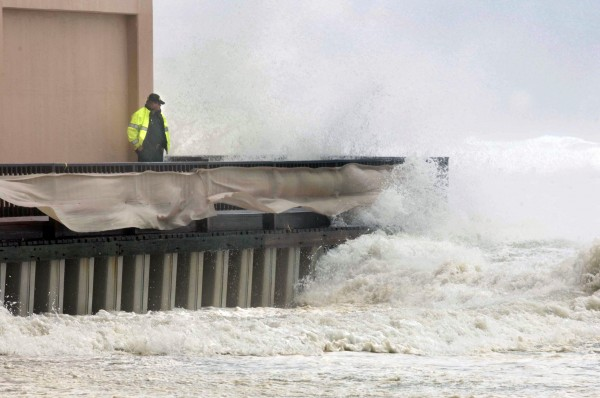 An unidentified Okaloosa County Deputy Sheriff stands next to the Jetty East condominium in Destin, Fla., Tuesday, Aug. 28, 2012 as a wave crashes over the buildings boardwalk. Although Isaac is expected to make landfall in Louisiana, the storm still pounded shorelines along Northwest Florida as it moved through the Gulf of Mexico.