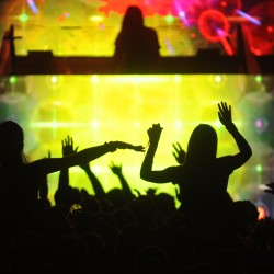 Revelers are silhouetted against the colorful light display of freeform dubstep electronic artist Lorin Ashton, better known as Bassnectar, who performed at KahBang on Bangor's waterfront Saturday night, Aug. 11, 2012.
