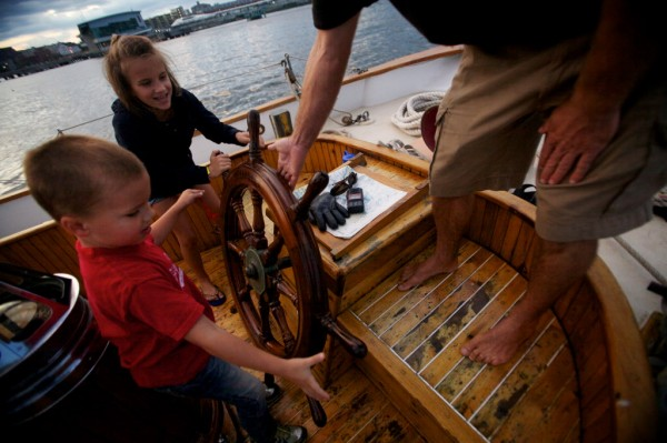 Emma Mitchell, 9, and brother Grant, 5, help turn the wheel aboard the Wendemeen on Portland Harbor on Monday night, Aug. 13, 2012. Capt. Ryan Langley also helps.