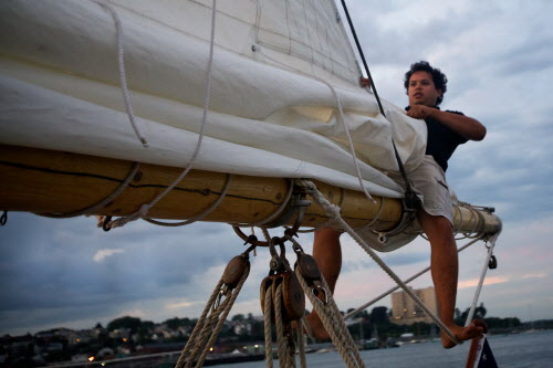 Nathan Pablo of the Portland Schooner Company furls a sail aboard the Wendemeen on Monday, Aug. 13, 2012 while returning to the Maine State Pier after the 6 p.m. cruise.
