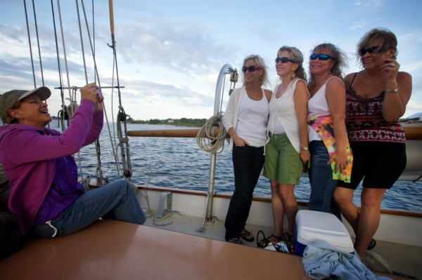 Bonnie Nather takes a picture for (from left) Stacey Smith, Veronika Benson, Merilee Smith and Emily Moore aboard the Wendameen on Monday night on Casco Bay. The 100-year-old schooner is owned by the Portland Schooner Company.