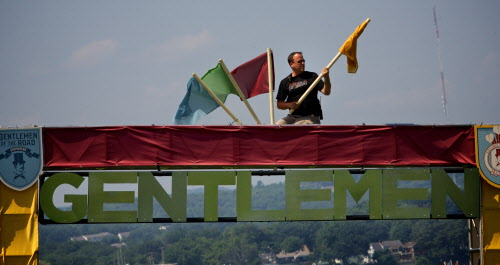 A workman who didn't want to give his name hangs flags atop the gate of a temporary concert venue springing up in Portland's Eastern Promenade park on Friday, Aug. 3, 2012 in preparation for the Mumford & Sons &quotGentlemen of the Road&quot tour stop Saturday.