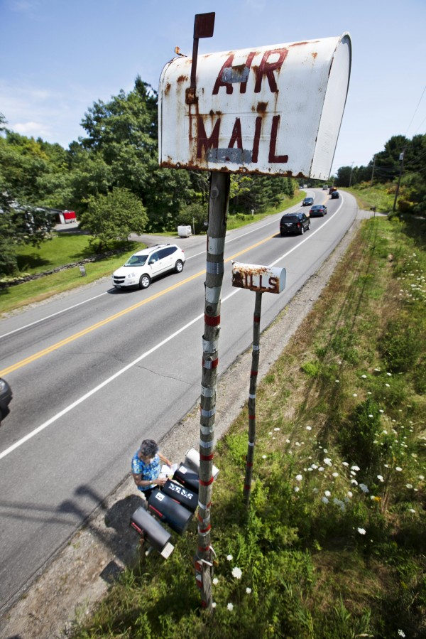 A landmark for 30 years, the &quotAIR MAIL&quot and &quotBILLS&quot mailboxes tower over Dorothy Howard as she picks up her mail, Saturday, Aug. 4, 2012, on Route 1 in Belfast. Her neighbor, the late Alden Horn, erected the boxes for the amusement of motorists.
