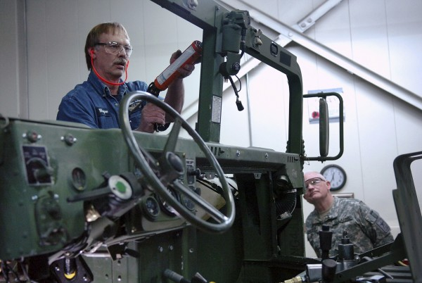 Mechanical technician Wayne Wasson prepares to install a windshield on a Humvee as Maj. Gen. Raymond Carpenter (right), director of the Army National Guard, watches at Maine Miliary Authority in Limestone on April 16, 2010.
