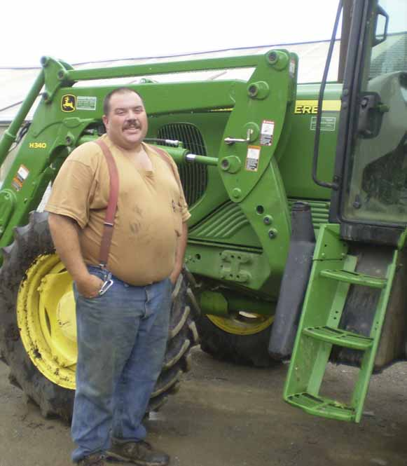 Jason Osborne, owner of the Osborne Family Farm in Charleston, stands next to one of his tractors.